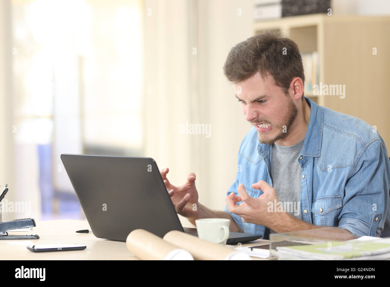Entrepreneur angry and furious with a laptop in a little office or home - Stock Image