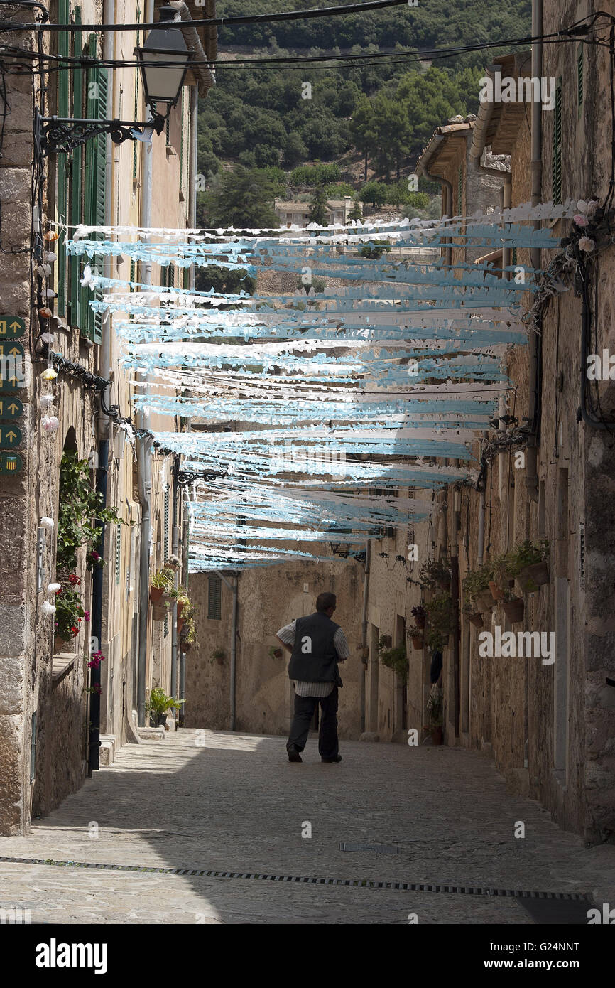 small village road with festivity decorations and passer by, Palma de Mallorca, Spain, seaside, summer, tourism, - Stock Image