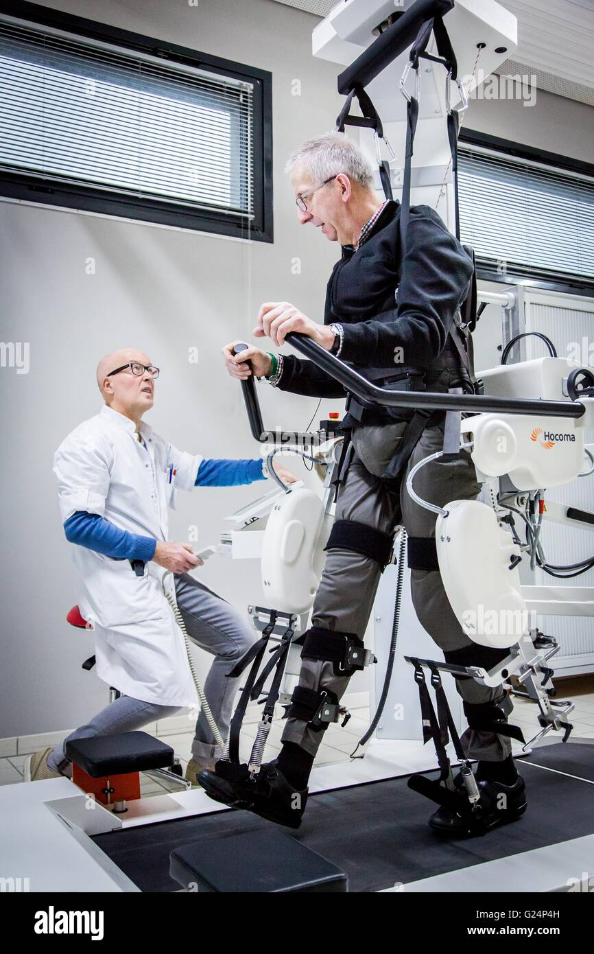 Robotic assistance with walking, Patient with multiple plaqueen rehabilitation session with the Lokomat robot. - Stock Image