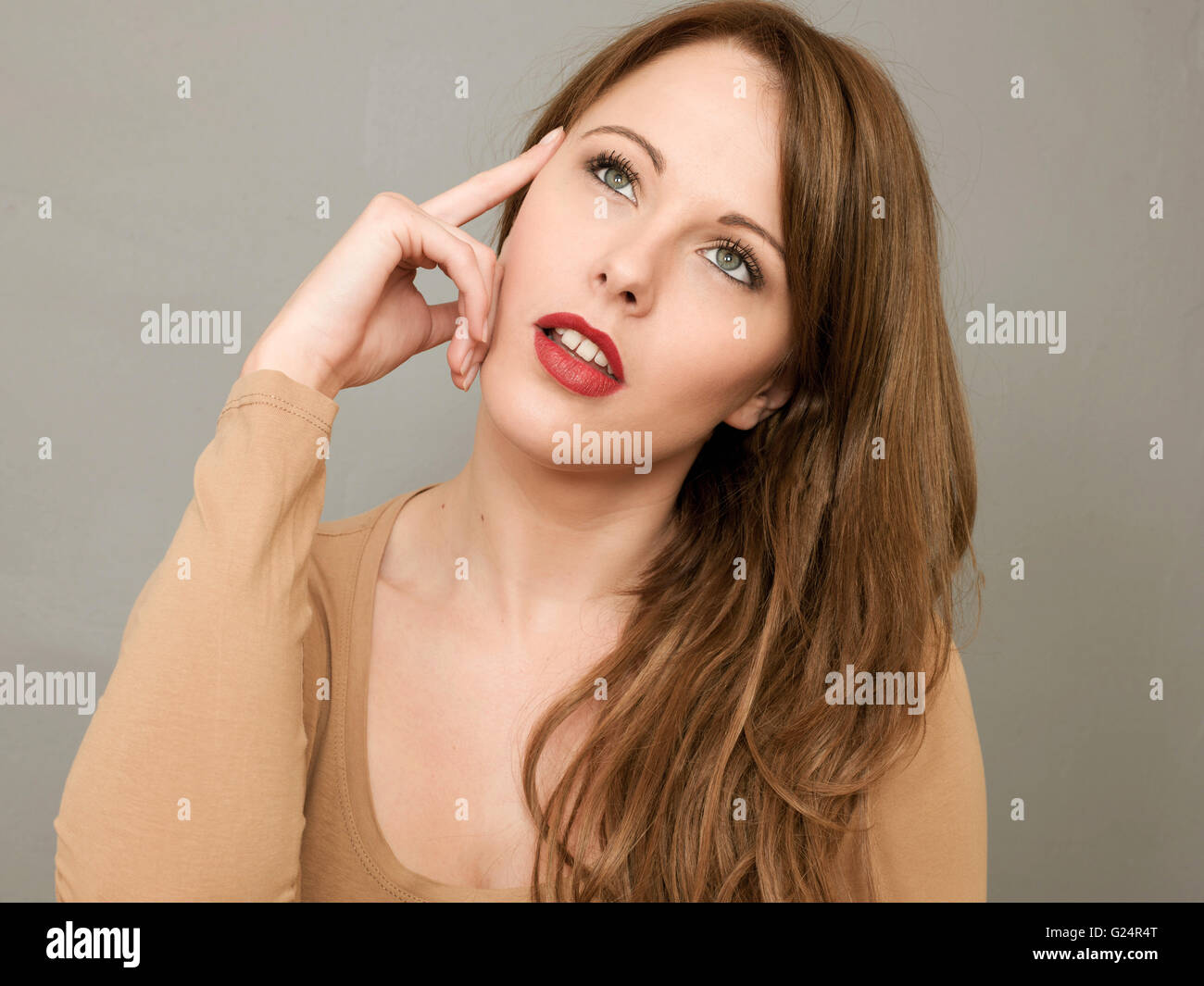 Portrait of a Woman Considering Choices or Options in a Thoughtful Pose Looking Up - Stock Image