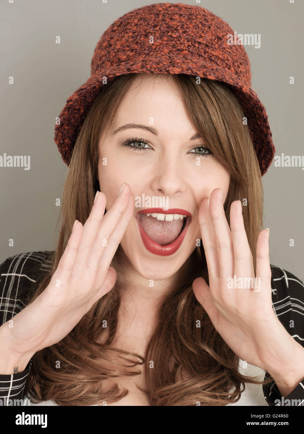 Portrait of a Woman Wearing a Red Woolen Hat Happy Pleased and Excited Shouting out Good News or Attracting Attention - Stock Image