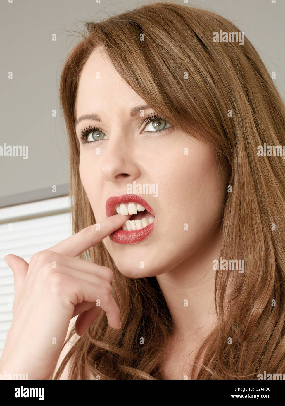 Portrait of a Worried Woman Biting Her Finger Nail Looking Unsure and Nervous - Stock Image