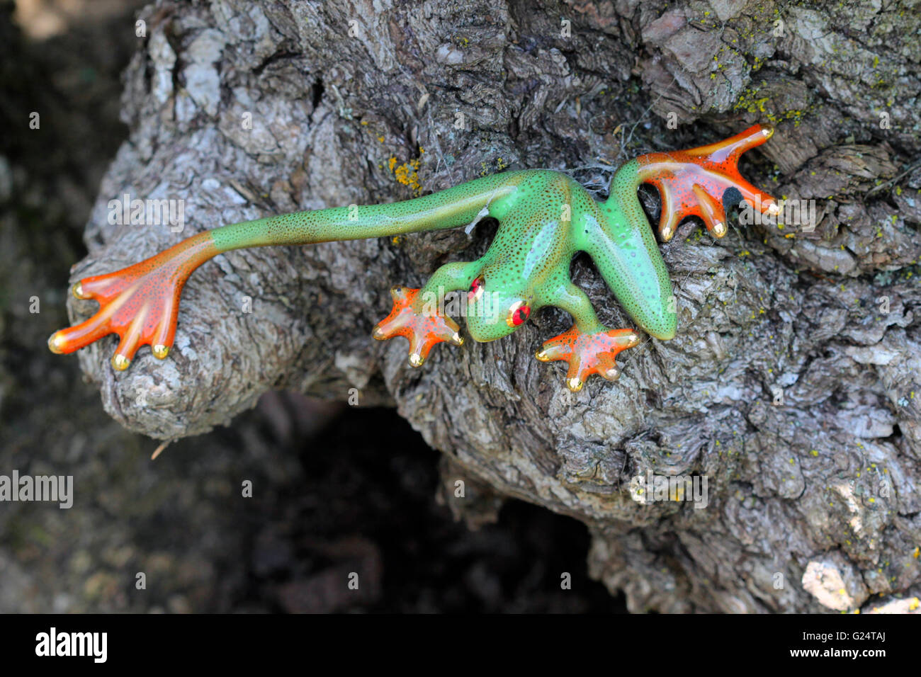 This ornamental green frog statue with orange feet is decorated with tiny small black spots. - Stock Image