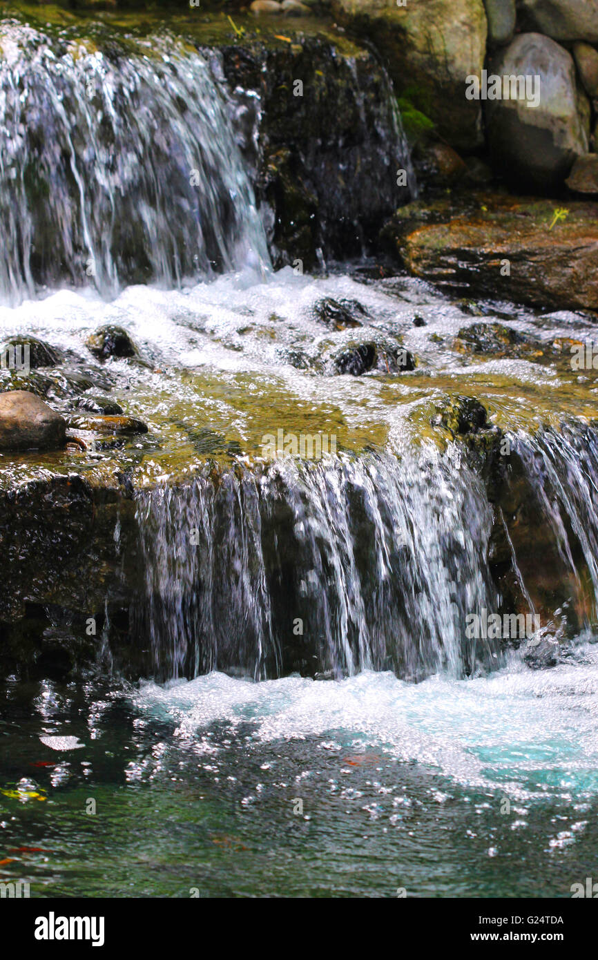 A garden pond supports a multi-tiered waterfall with many layers of rock slabs. - Stock Image