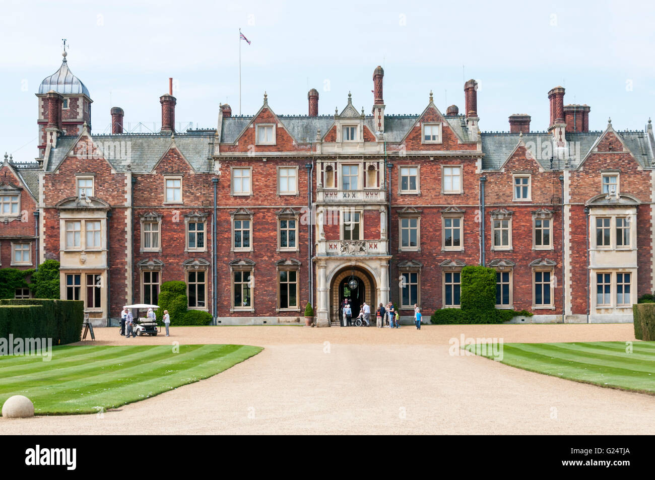 The north front entrance to Sandringham House with a tour party arriving and a shuttle from the car park. - Stock Image