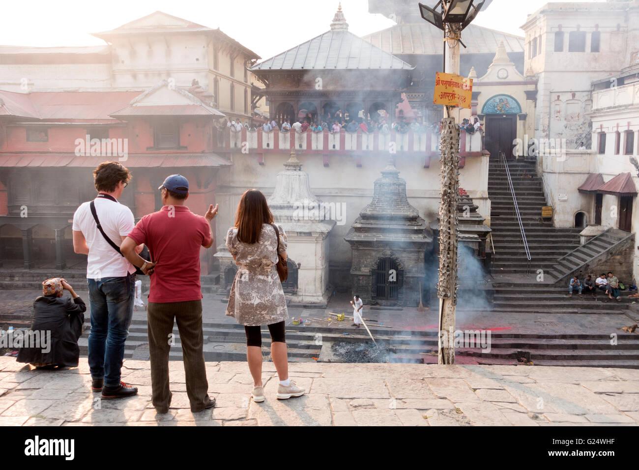 Tourists at the Pashupatinath Temple watching cremations, Kathmandu, Nepal - Stock Image