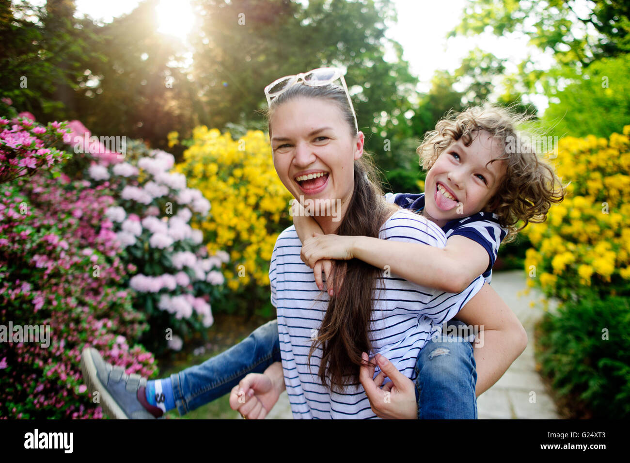 Older sister with his brother playing in the park - Stock Image