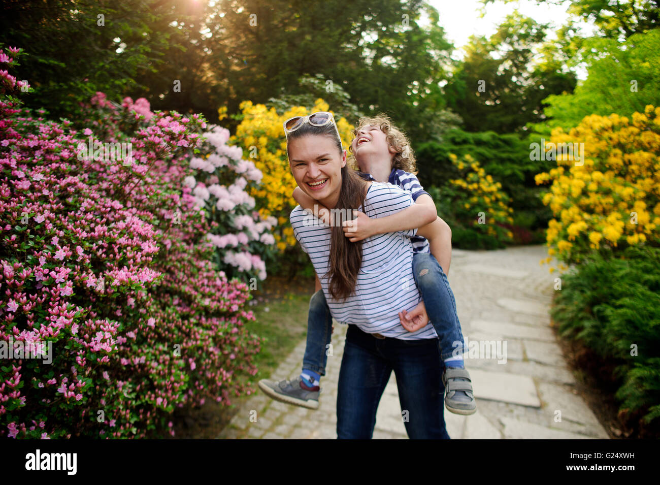 The young woman holds the boy on shoulders - Stock Image