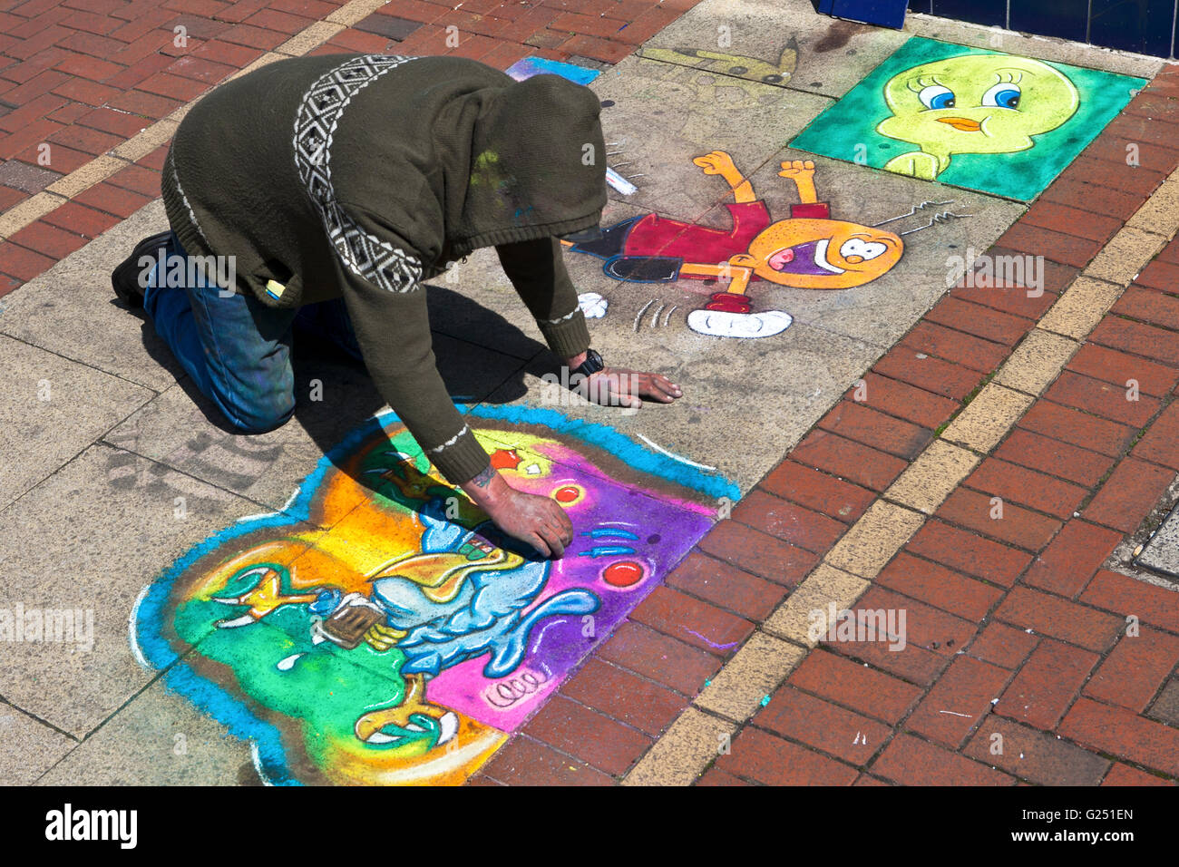 A man knelt down chalk drawing on art, artwork on pavement, Fleetwood, Thornton-Cleveleys, Flyde Coast, Lancashire, - Stock Image