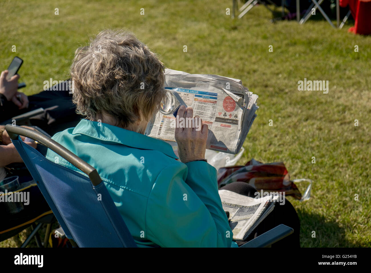 A lady checks the form guide at Chester Racecourse, Chester, Cheshire, UK - Stock Image
