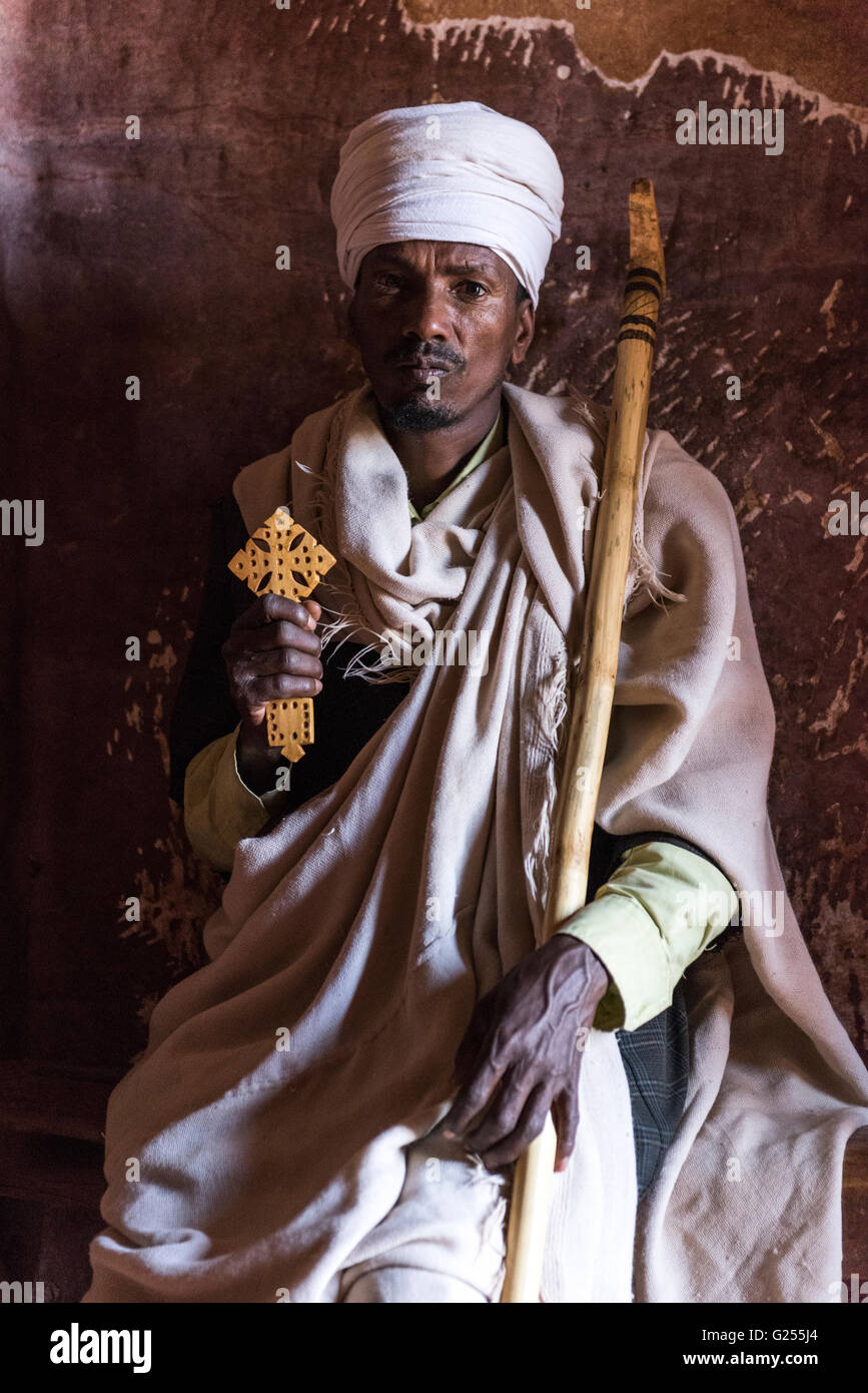 Orthodox Priest holding holy cross inside rock-cut churches Gheralta, Ethiopia - Stock Image