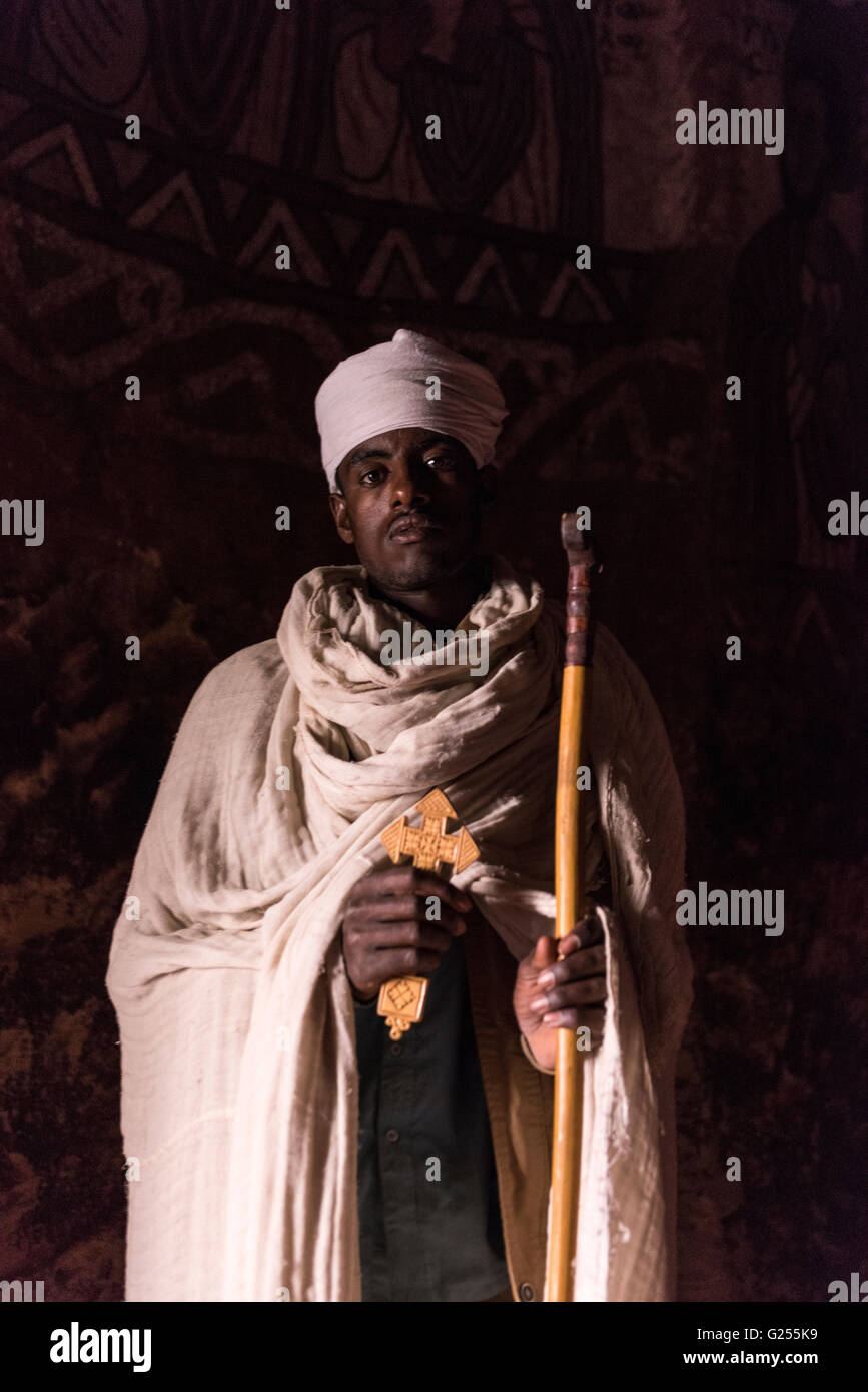 Orthodox Priest holding a cross inside rock hewn church Gheralta, Ethiopia - Stock Image
