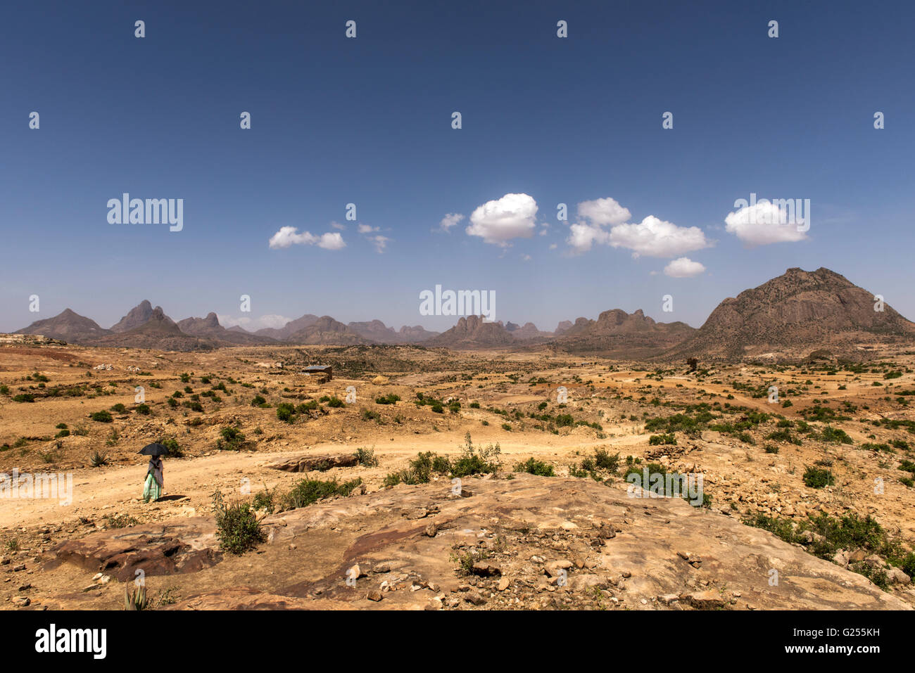 View of Gheralta with woman walking in the foreground, Ethiopia - Stock Image
