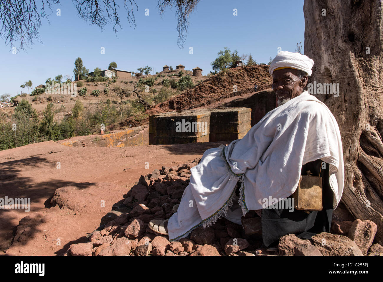 Portrait of local man with Saint George rock-cut church in the background Lalibela, Ethiopia - Stock Image