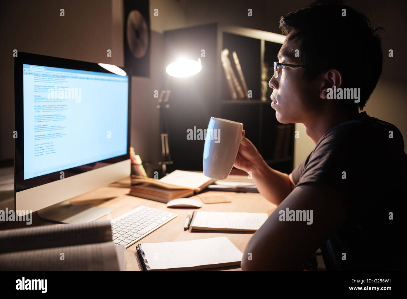 Profile of handsome asian young man studying with computer and drinking tea in dark room - Stock Image
