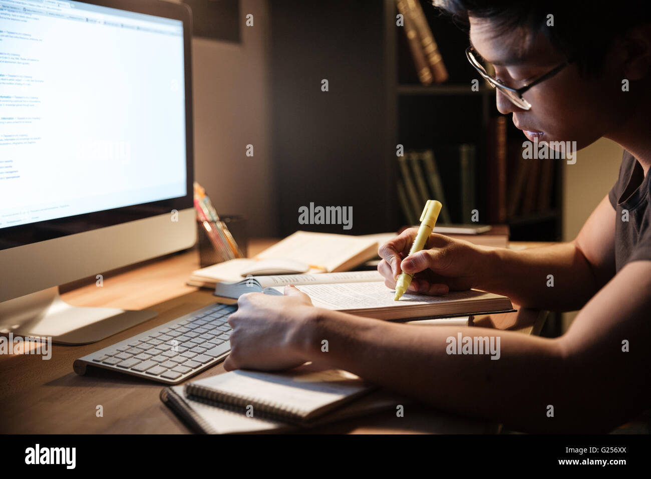 Serious asian young man studying with books and computer in dark room at home - Stock Image