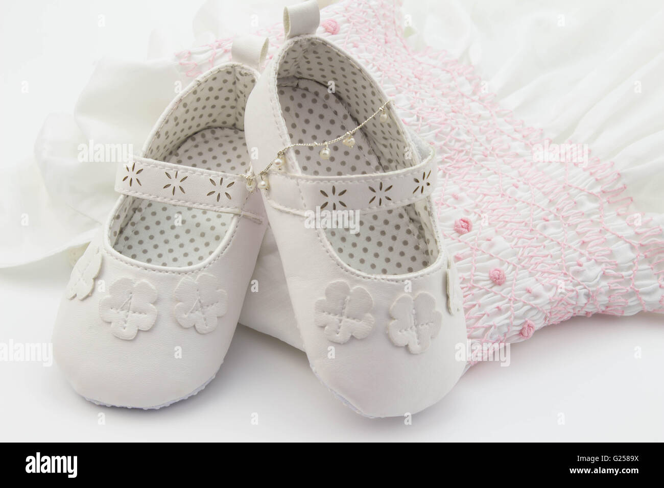 Pair of white baby shoes on embroidered white and pink dress and pearl bracelet - Stock Image