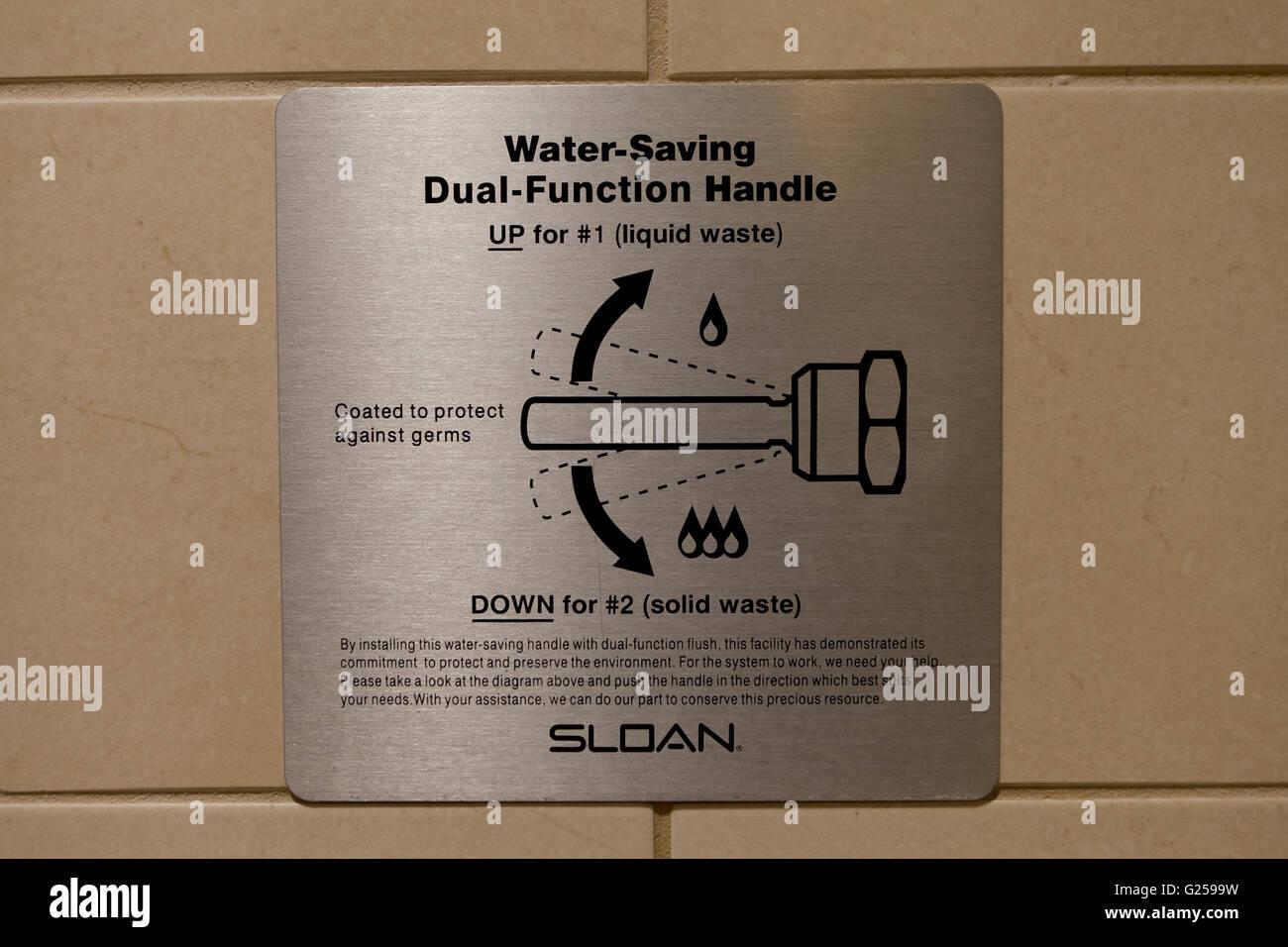 Water saving dual function public toilet handle notice - USA - Stock Image