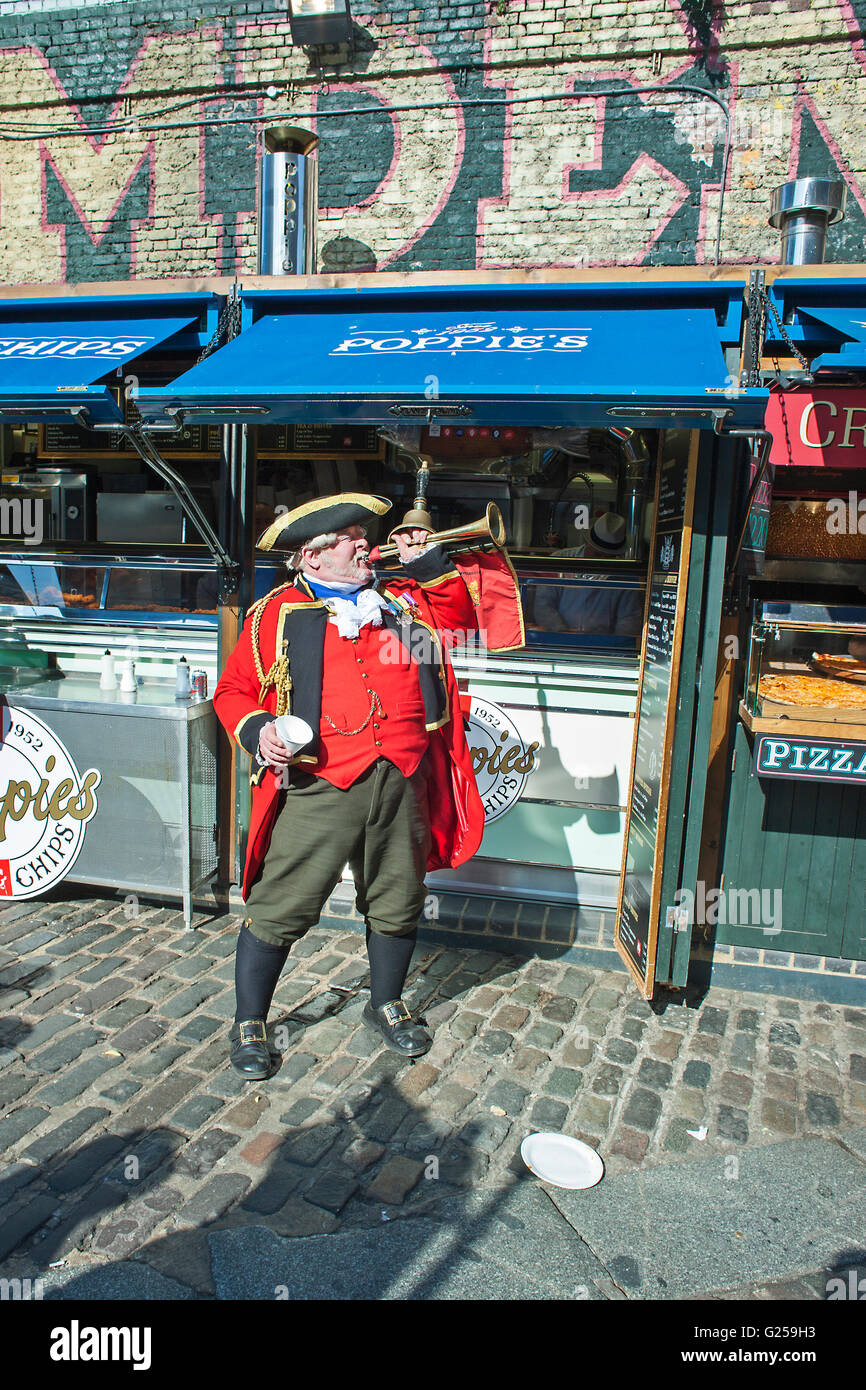 Town Crier blowing bugle trumpet, red livery and buckled shoes, red waistcoat, Tricorne hat - Stock Image