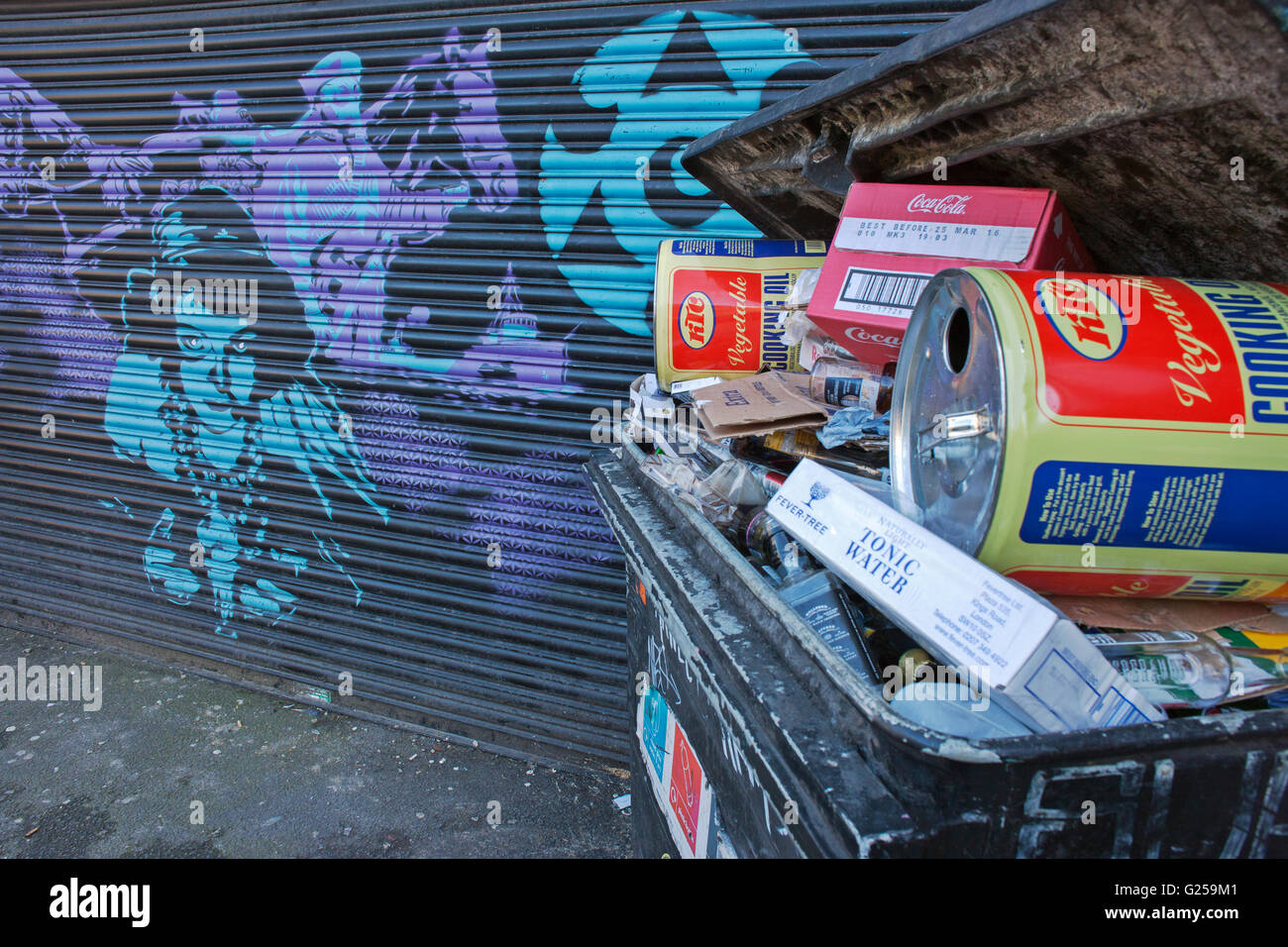 'no Dumping', Industrial cooking oil drums in waste bin by mural Camden town - Stock Image