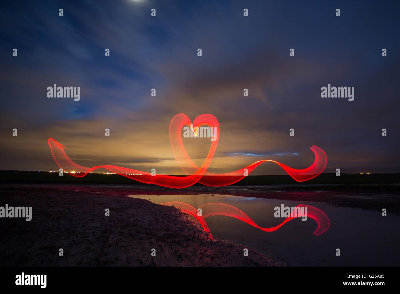 red heart shape light trail in night landscape, France - Stock Image