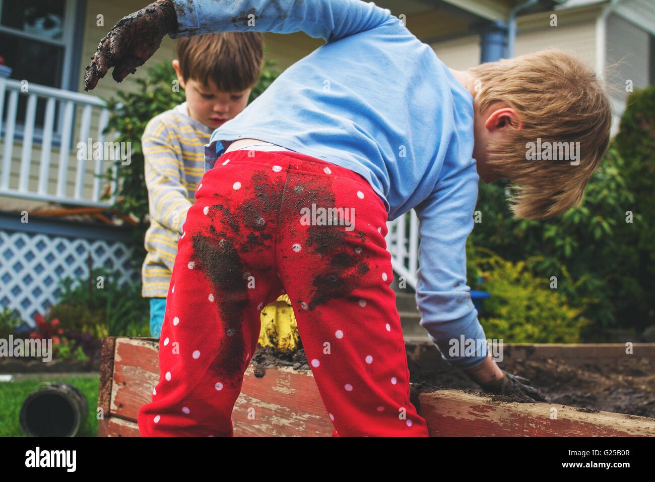 Two boys covered in mud gardening - Stock Image