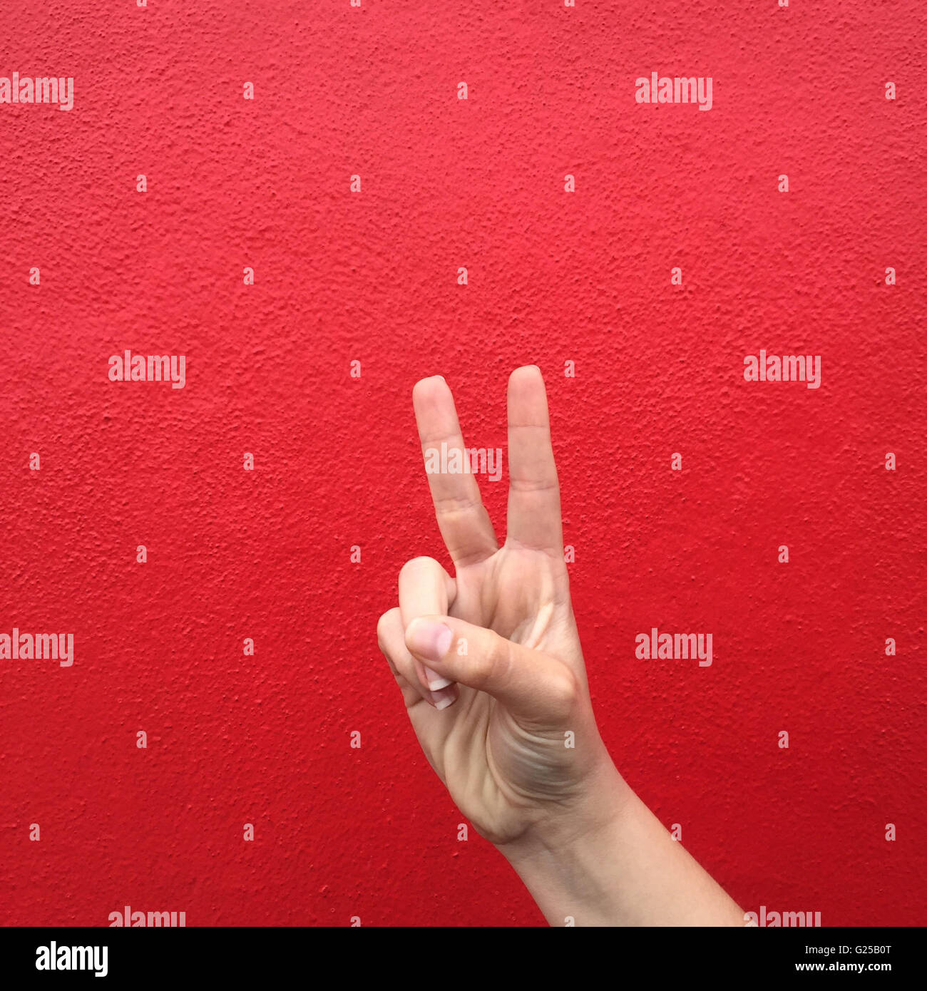 Woman's Hand making victory sign against red wall - Stock Image