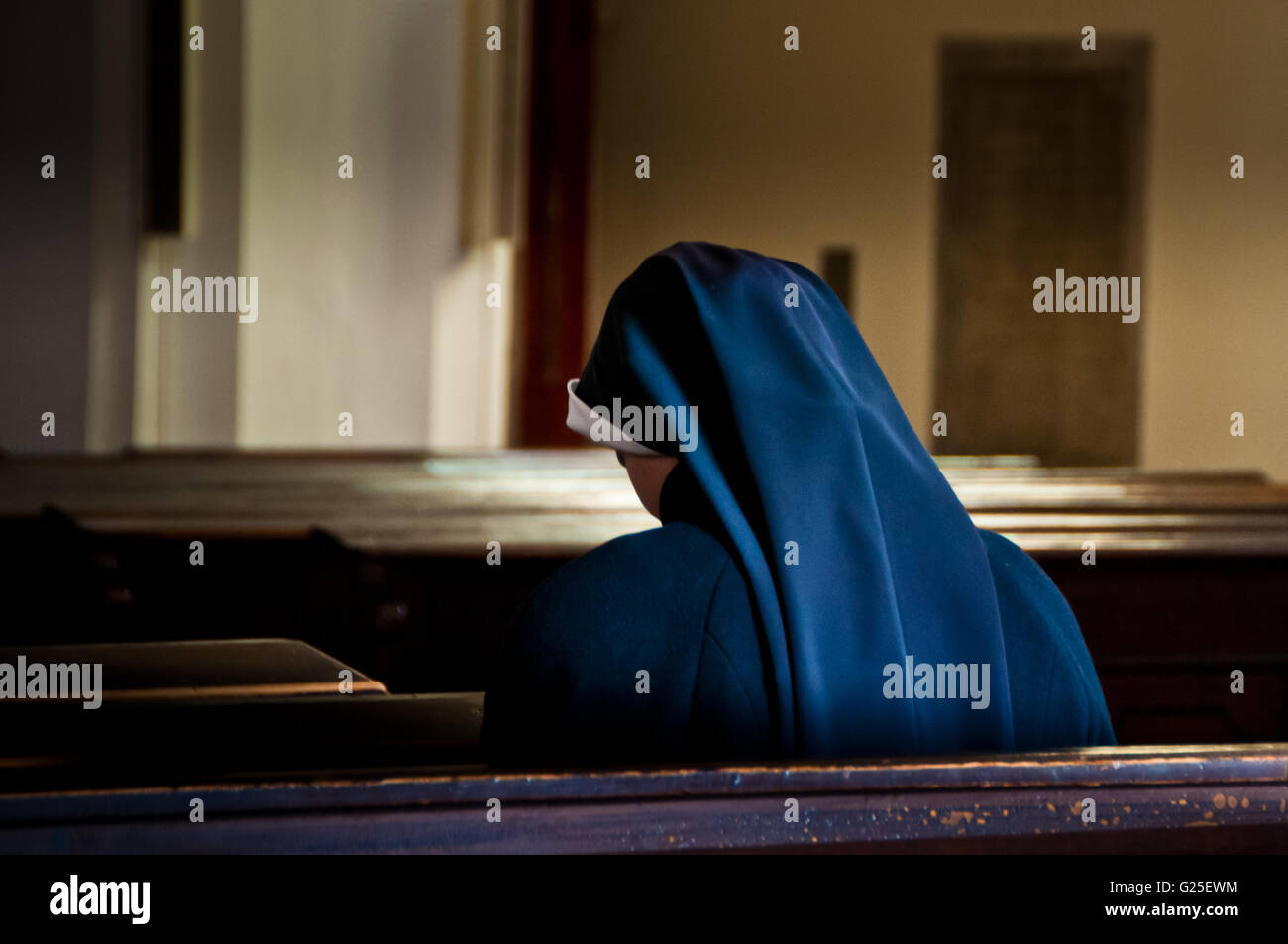nun sitting in a church praying - Stock Image