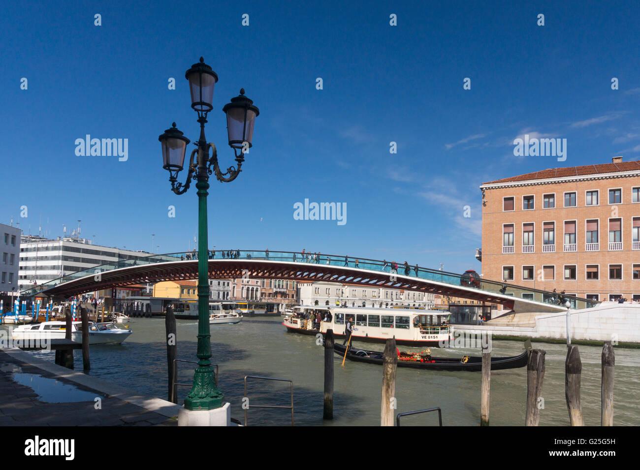 A gondoler passes in front of Constitution Bridge, Venice - Stock Image