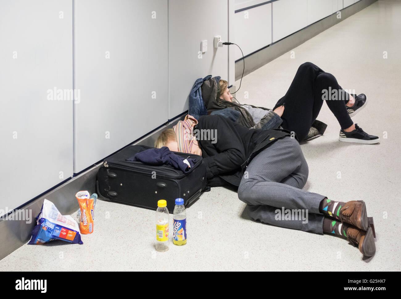 Two young men sleeping on airport terminal floor. UK - Stock Image