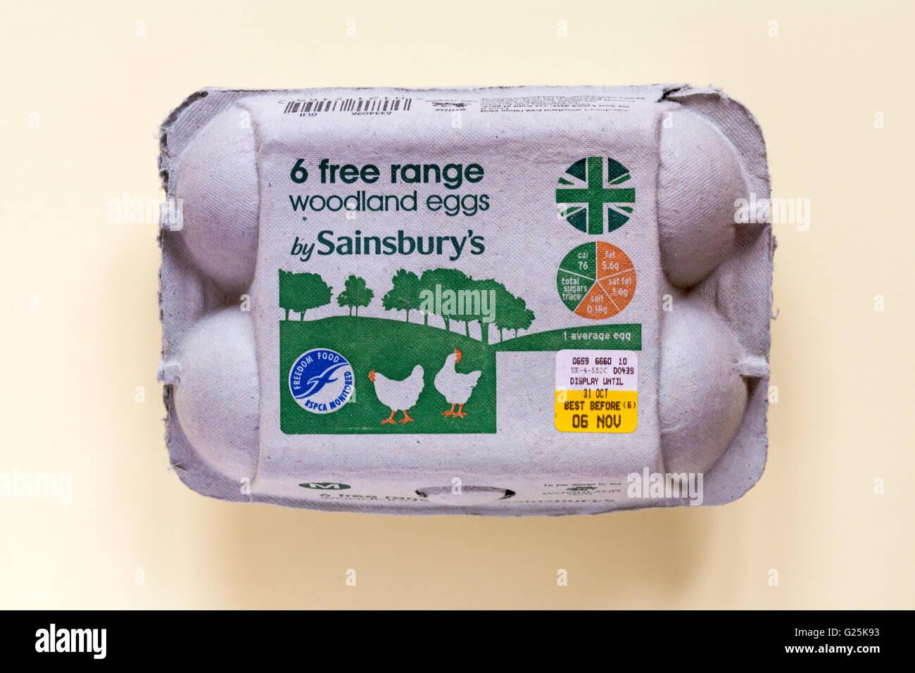Carton of 6 free range woodland eggs by Sainsburys isolated on pale yellow background Stock Photo