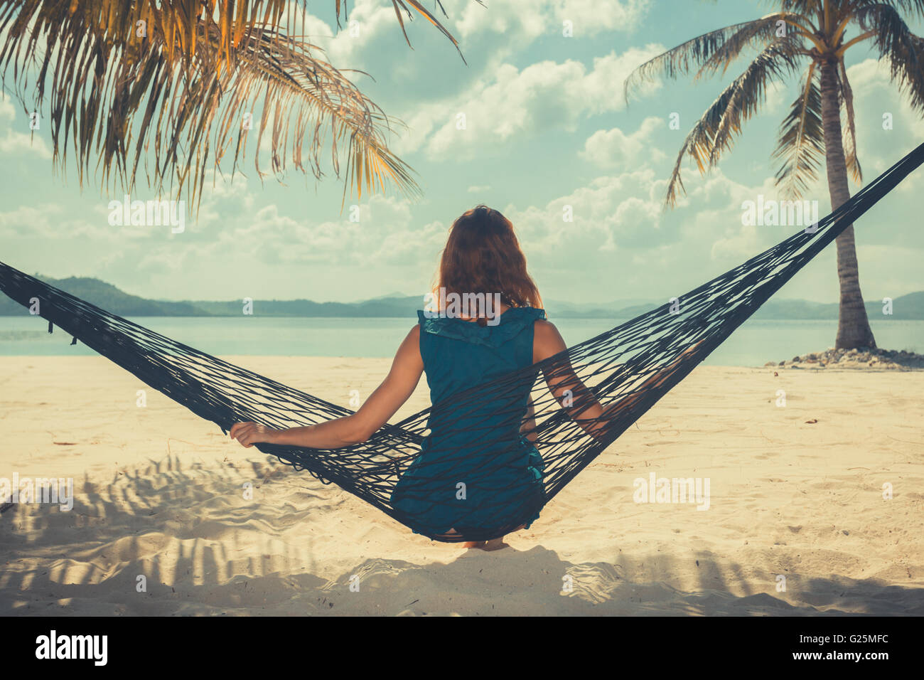 Vintage filtered shot of a young woman sitting in a hammock on a tropical beach - Stock Image