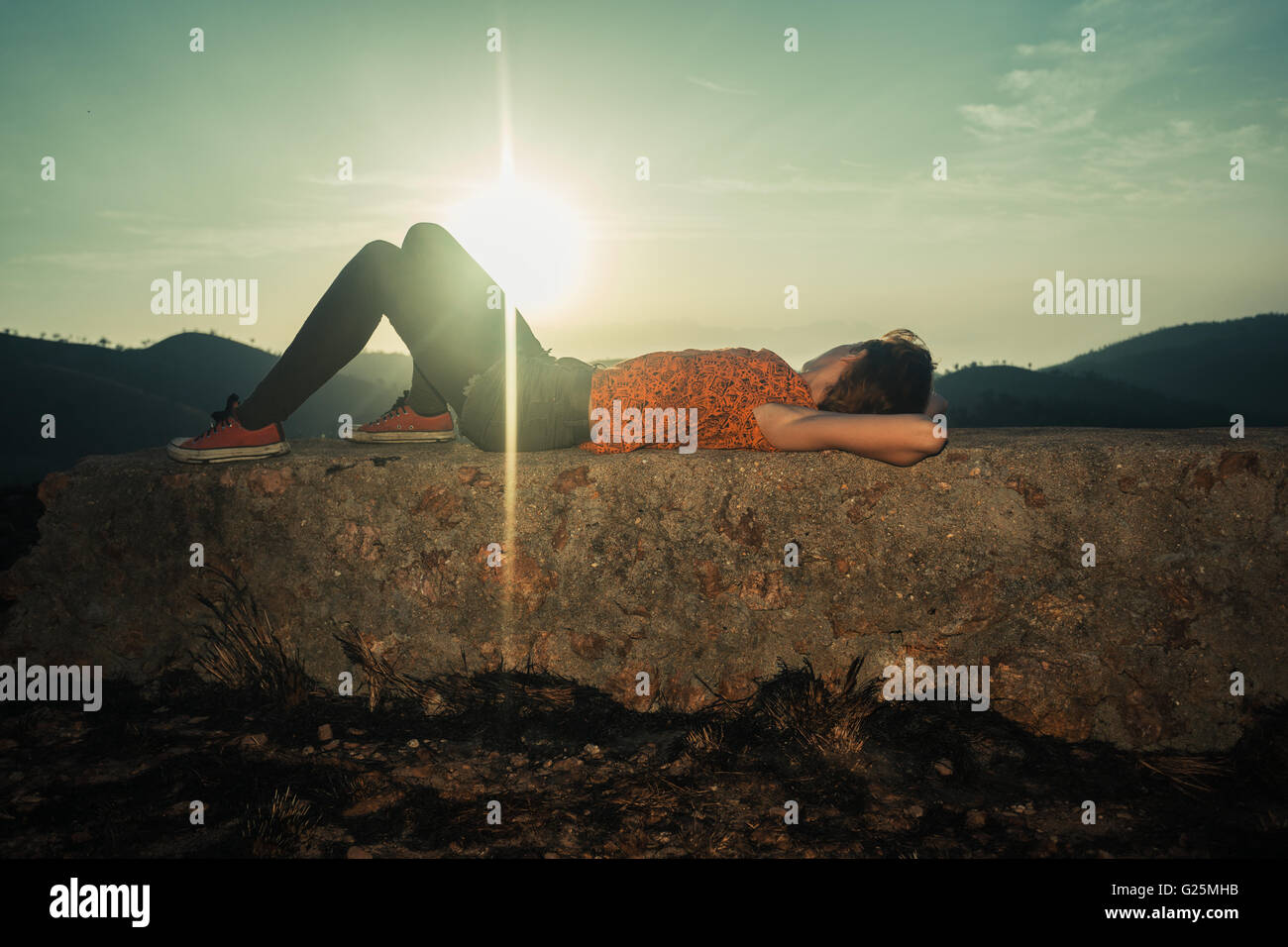 A young woman is lying on an unusual rock at sunrise - Stock Image