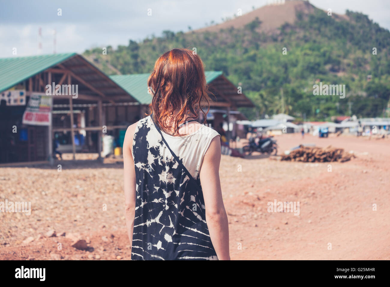 A young caucasian woman is walking around a small town in a developing country - Stock Image