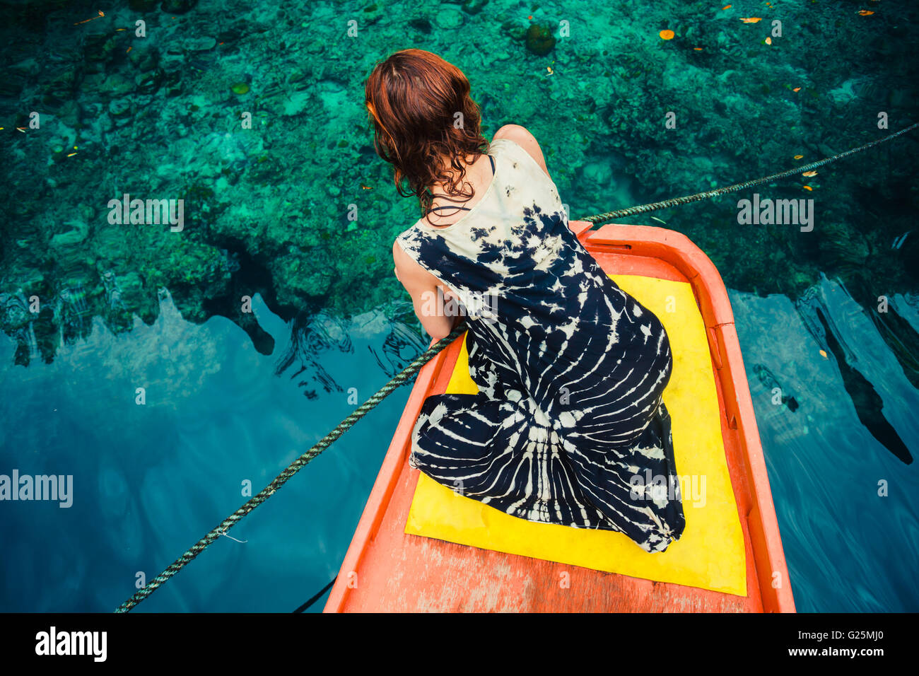 A young woman is sitting on a boat and is looking at the clear blue water - Stock Image