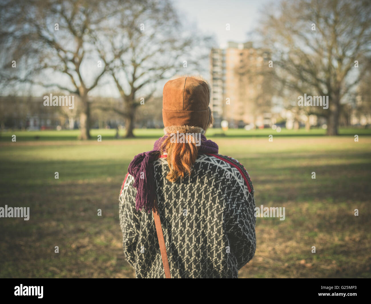 A young woman is walking in the park on a winter's day - Stock Image