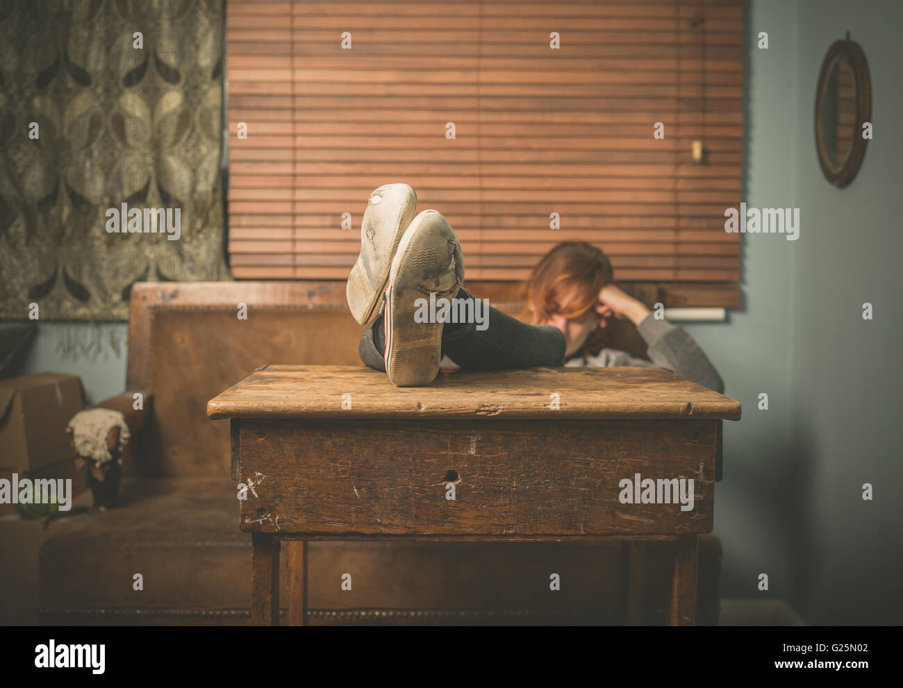 A young woman wearing worn out shoes is resting her feet on a table at home - Stock Image