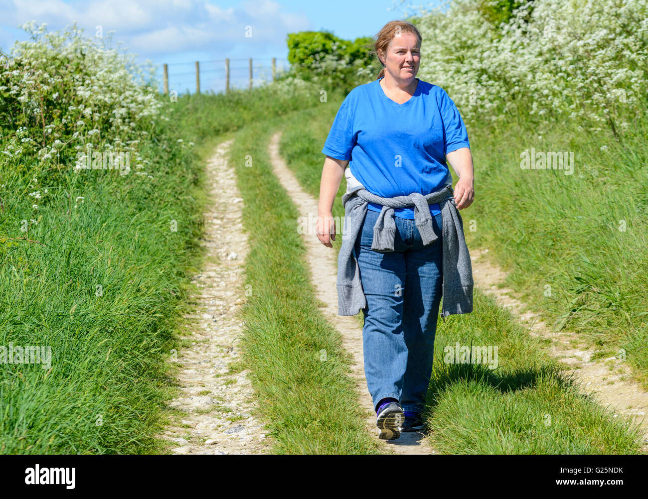 Weight loss. Middle aged woman walking along a country path in the summer.Healthy living. Healthy lifestyle. Getting - Stock Image
