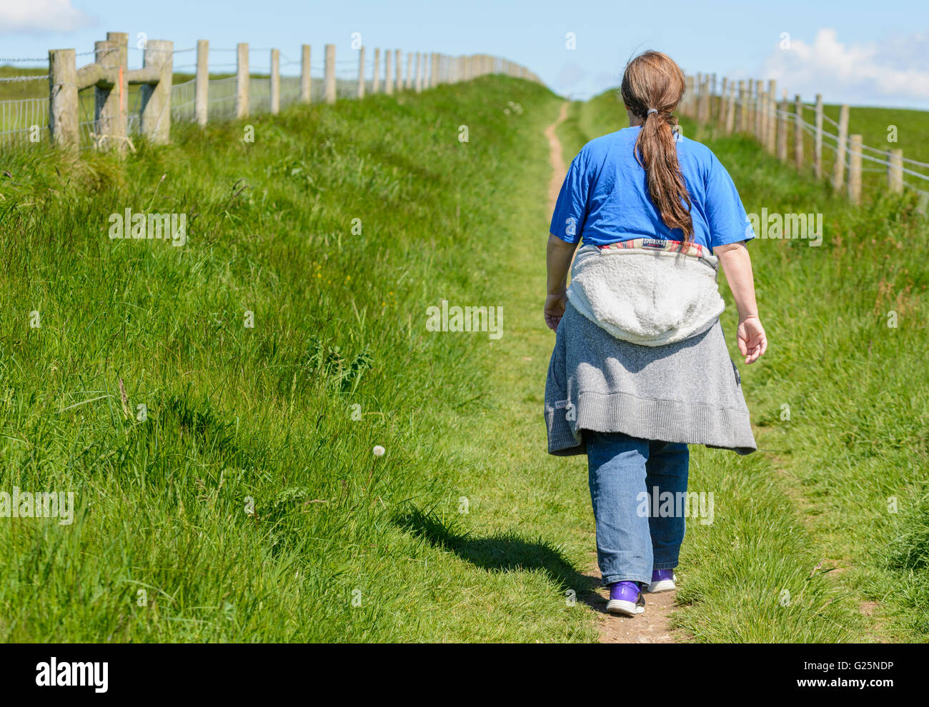 Losing weight. Woman walking away along a country path. Healthy living. Healthy lifestyle. Getting fitter. Keeping - Stock Image