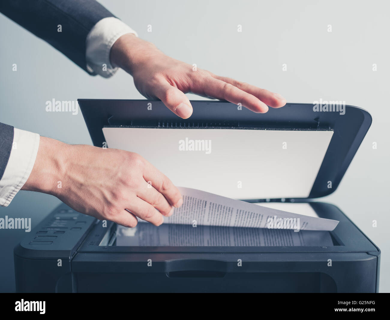 The hands of a young businessman is placing a document on a flatbed scanner in preparation for copying it - Stock Image