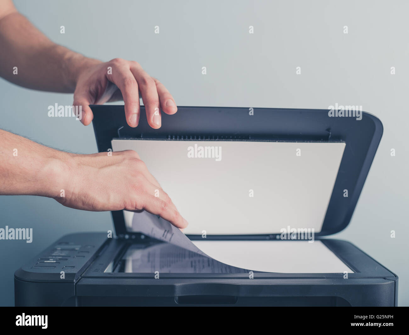 The hands of a young man is placing a piece of paper on a flatbed scanner in preparation for copying it - Stock Image