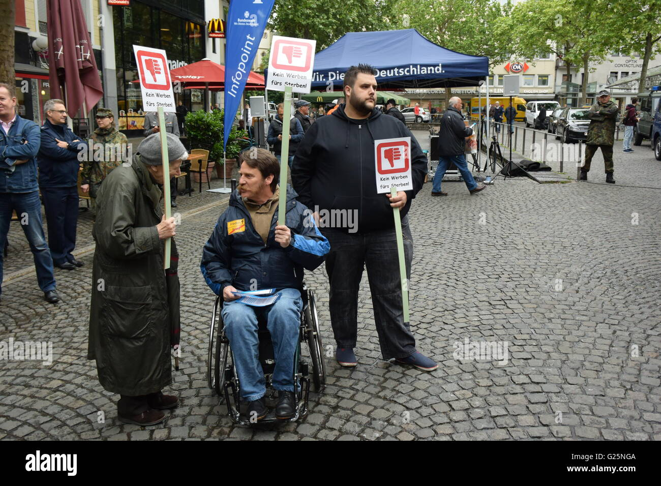 some people demonstrate against the advertising of the German Bundeswehr on the Friedensplatz in Bonn, Germany - Stock Image