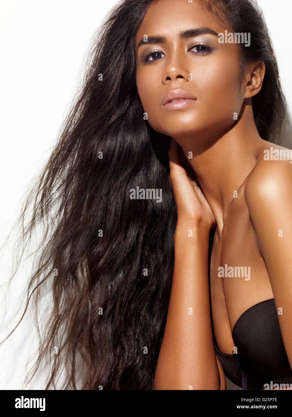 Young woman with long black hair wearing a black bra - Stock Image