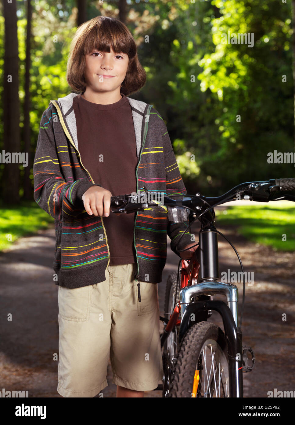 Boy, ten years, standing next to his bicycle - Stock Image