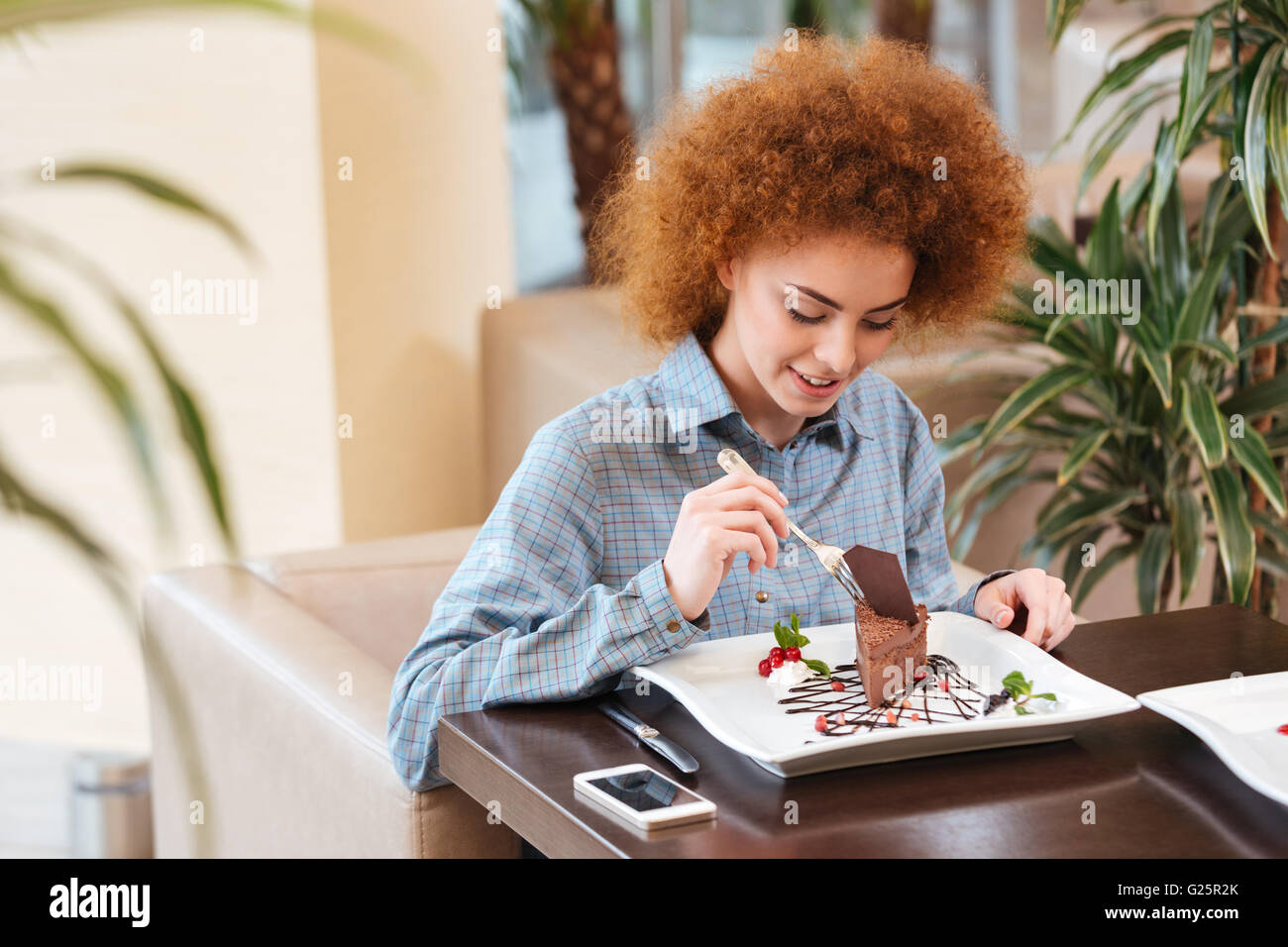 Cute curly young woman with red hair eating dessert in cafe - Stock Image