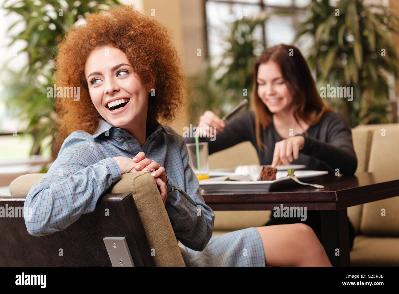 Two cheerful beautiful young women sitting in cafe and laughing together - Stock Image