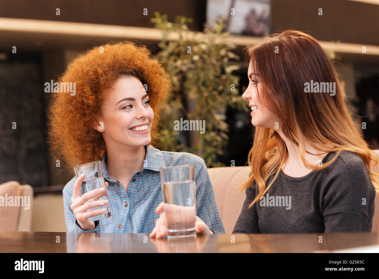 Two happy attractive young women smiling and drinking water in cafe - Stock Image