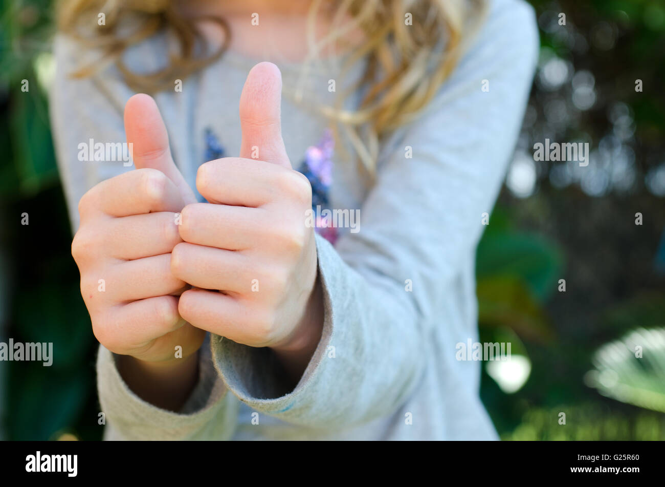 Close up of child giving two thumbs up - Stock Image