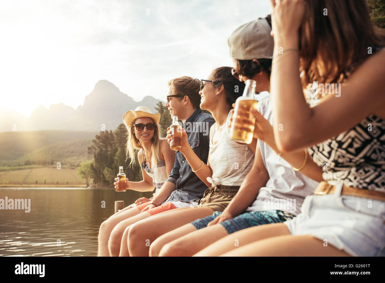 Portrait of young men and woman sitting on jetty with beers. Young men and woman enjoying a day at the lake. - Stock Image