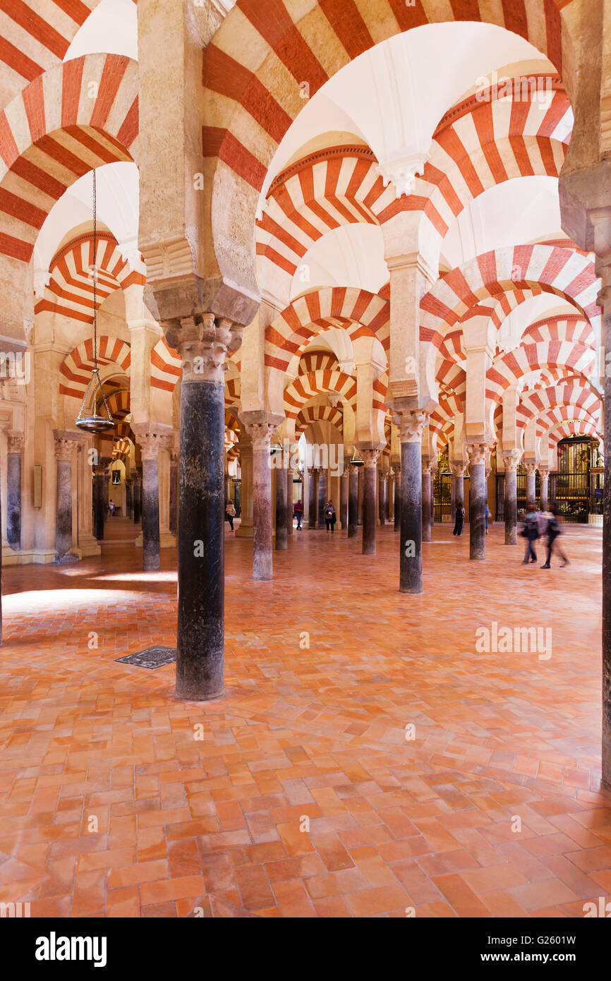 Columns at the Mezquita-Cathedral of Cordoba, Spain. Visitors walking around and taking photos. - Stock Image